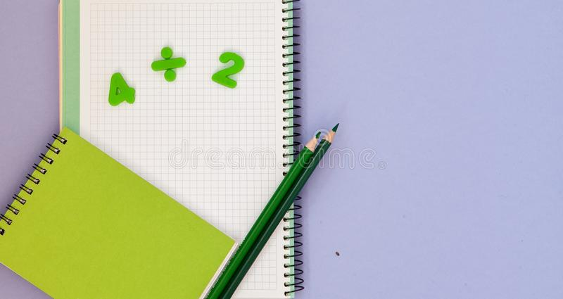 Learning maths. Kid`s desk with blank notebook, colorful pencils and numbers top view with copy space royalty free stock photos