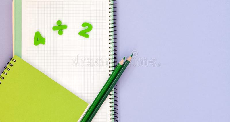Learning maths. Kid`s desk with blank notebook, colorful pencils and numbers top view with copy space stock photo