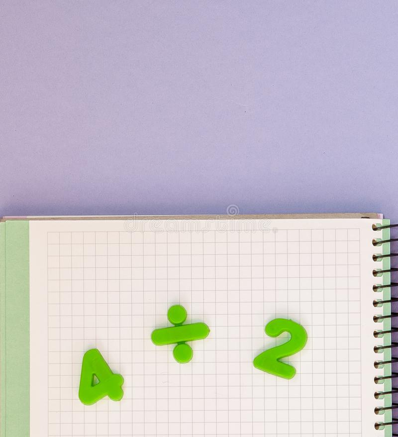 Learning maths. Kid`s desk with blank notebook and numbers top view with copy space stock photo