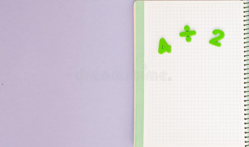 Learning maths. Kid`s desk with blank notebook and numbers top view with copy space royalty free stock images