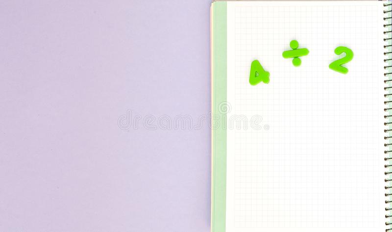 Learning maths. Kid`s desk with blank notebook and numbers top view with copy space stock photography