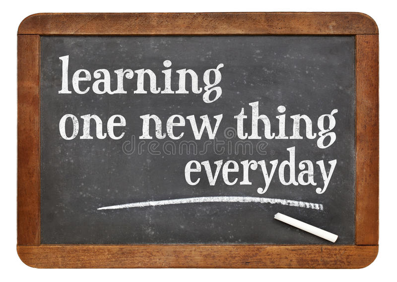 Learning one new thing everyday. Motivational text on a vintage slate blackboard stock images