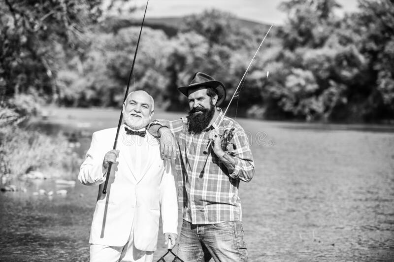 Learning from the professional. hobby of businessman. retirement fishery. friends men with fishing rod. Fly fishing. Adventures. happy fishermen in water stock image