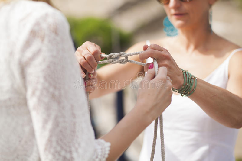 Learning sea knots. One girl teaches the knitting of knots another girl stock photography