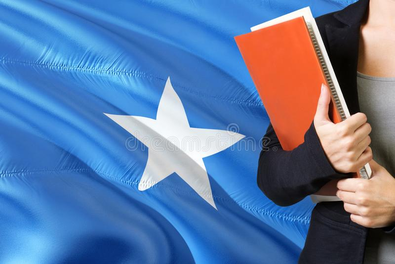 Learning Somalian language concept. Young woman standing with the Somalia flag in the background. Teacher holding books, orange royalty free stock photos