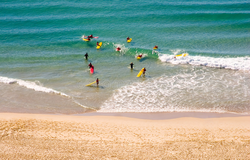 Learning at surf school. Young people learning to surf at a surf school, teachers in the ocean water with them stock photos
