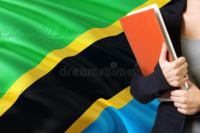 Learning Tanzanian language concept. Young woman standing with the Tanzania flag in the background. Teacher holding books, orange. Blank book cover royalty free stock photography