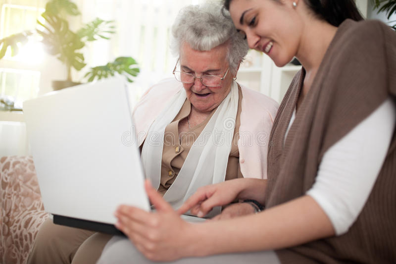 Learning things is good for the ageing brain. Young women showing how to use laptop to an old person royalty free stock photo