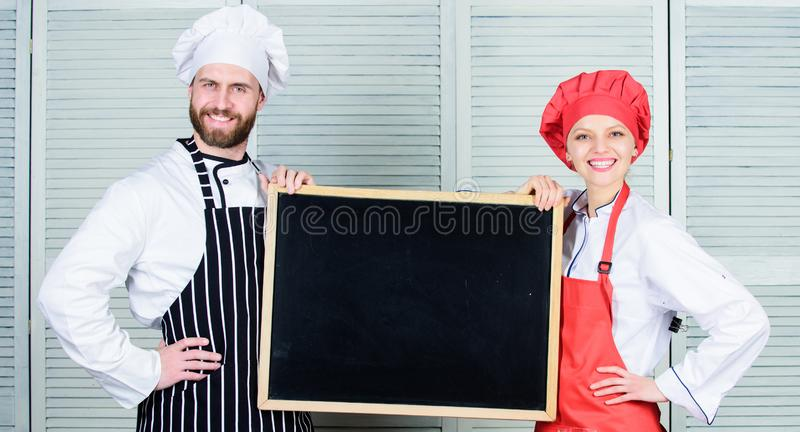 Learning to cook through cook. Master cook and kitchen maid giving cooking class. Couple of man and woman holding empty royalty free stock image