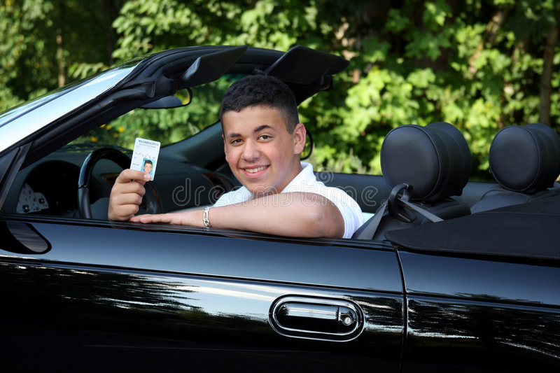 Learning to Drive. A teenage boy in a convertible holding his drivers permit royalty free stock photo