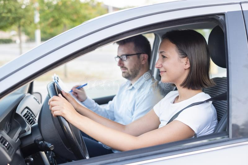 Learning to drive a car. Driving school. Instructor and young female student, driving lesson royalty free stock photo