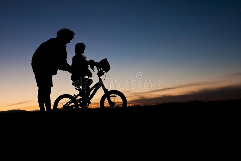 Learning to Ride A bike. A parent helps her young child with learning to ride a bike