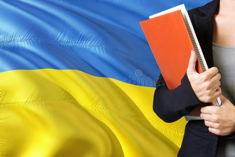 Learning Ukrainian language concept. Young woman standing with the Ukraine flag in the background. Teacher holding books, orange stock photo