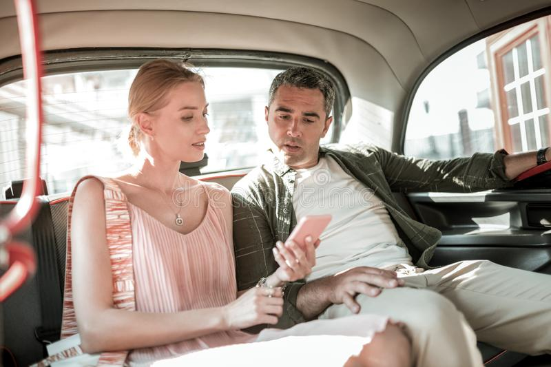 Woman showing her husband their route on her smartphone. royalty free stock photography