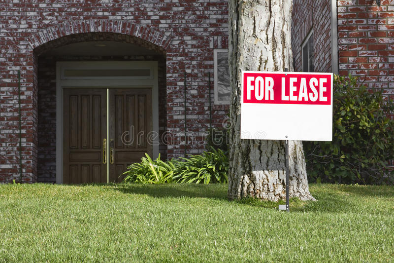 For Lease. Lease sign in the front yard of a house royalty free stock photo