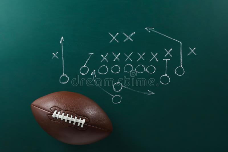 Leather American football on chalkboard royalty free stock photography
