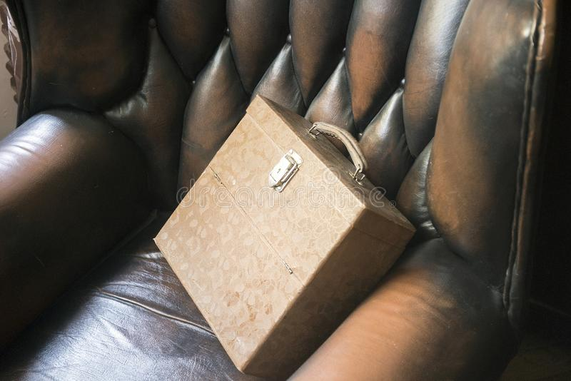 Leather armchair and old briefcase. Leather armchair with old briefcase or box, indoor close-up royalty free stock photography