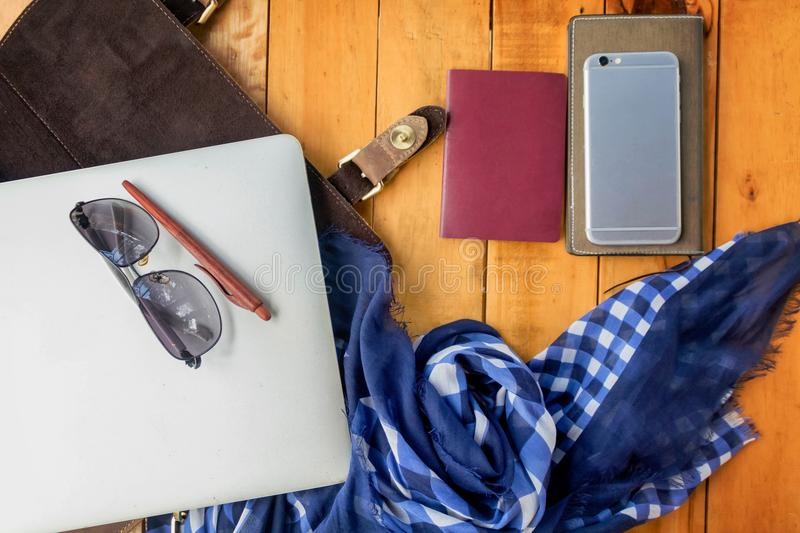 Leather bag notebook and blue check scarf on wood table stock images