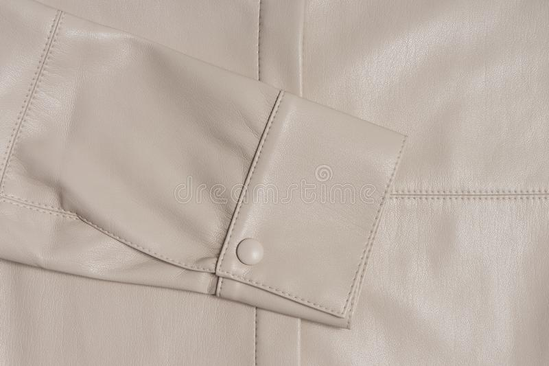 Leather beige sleeve on a stitched material. stock photo