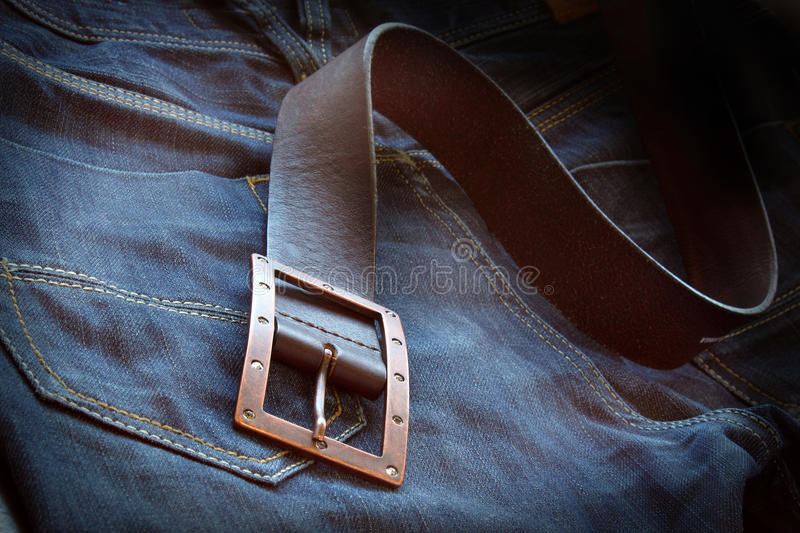 Leather belt over a pair of jeans. With vignette, vintage style stock photo