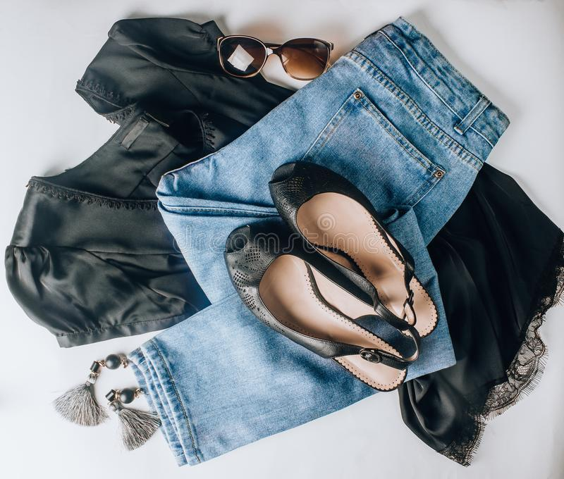 Leather black shoes, blue jeans, black silk t-shirts, sunglasses and earrings. Fashion concept.Flat lay. Womens fashion clothing, shoes accessories, leather stock image