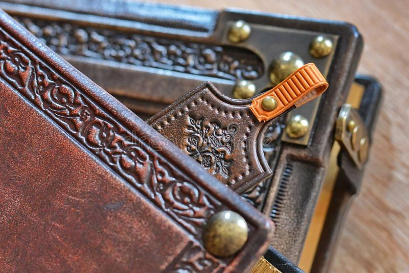 Leather bookmark peek out of the leather book stock photos