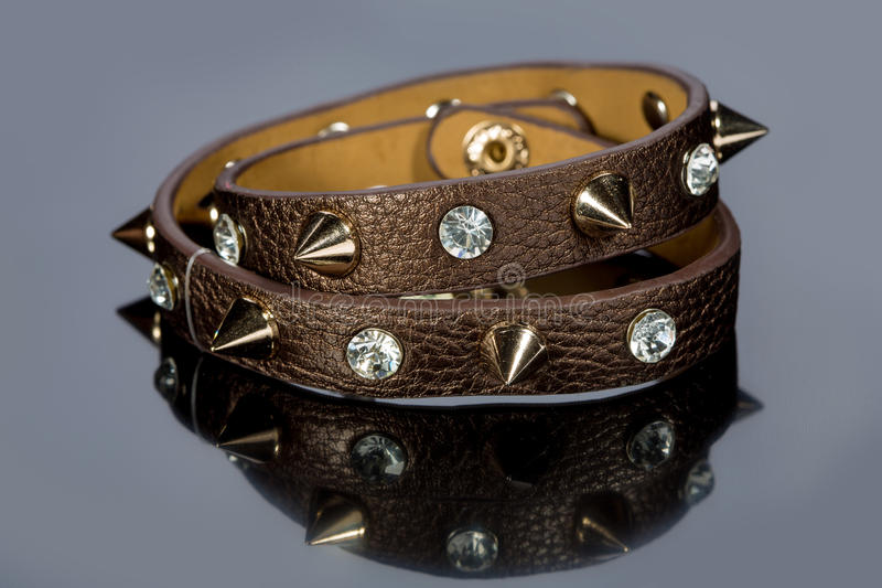 Leather bracelet with crystals. On a gray background royalty free stock photos
