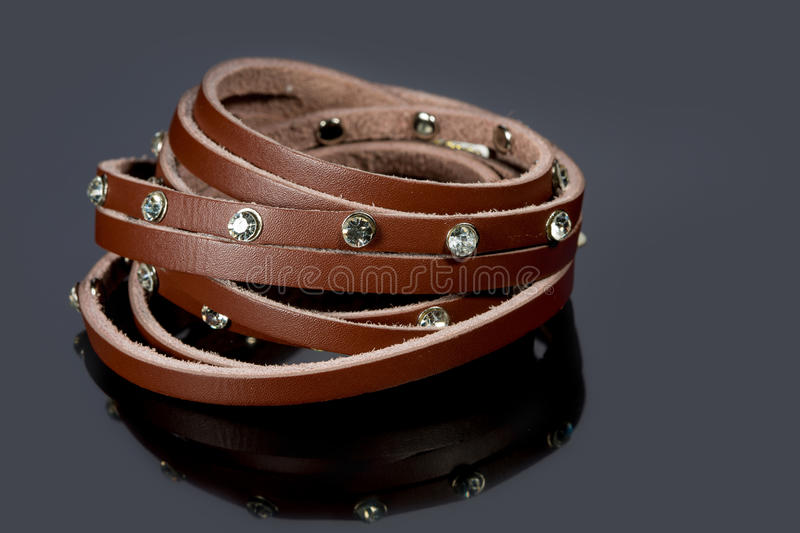 Leather bracelet with crystals. On a gray background stock image