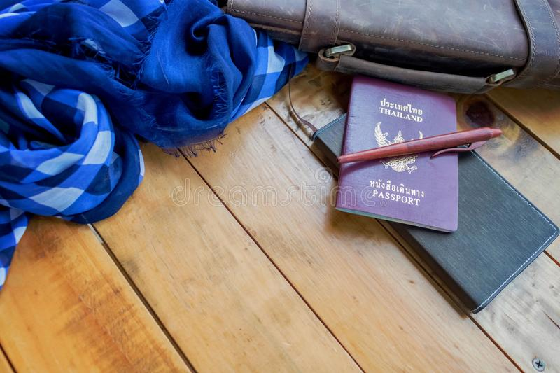 Leather brown bag passport and notebook with navy blue checked scarf. royalty free stock image