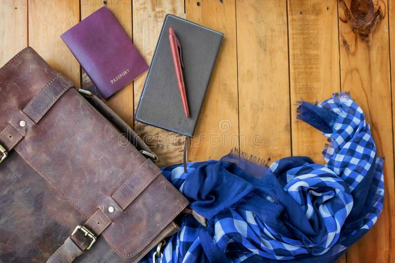 Leather brown bag passport and notebook with navy blue checked scarf. stock photography