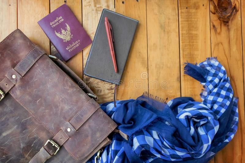 Leather brown bag passport and notebook with navy blue checked scarf. royalty free stock images