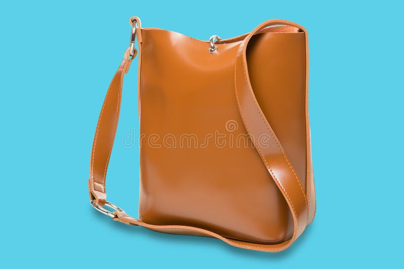 Leather brown women`s handbag with a long handle, on a turquoise background stock photography