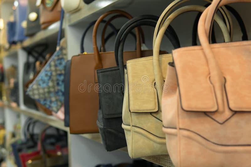 Leather and chamois bags on shelf, handbag shop royalty free stock images