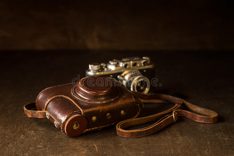 Leather cover and old 35mm camera. Still life with old leather cover and photo camera. Old rangefinder 35mm camera from WWII era royalty free stock image