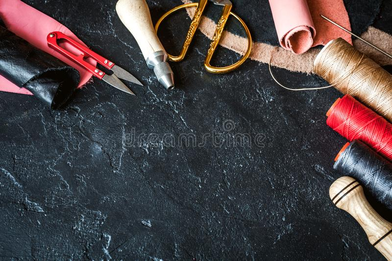 Leather craft instruments on dark background top view mock up stock photo