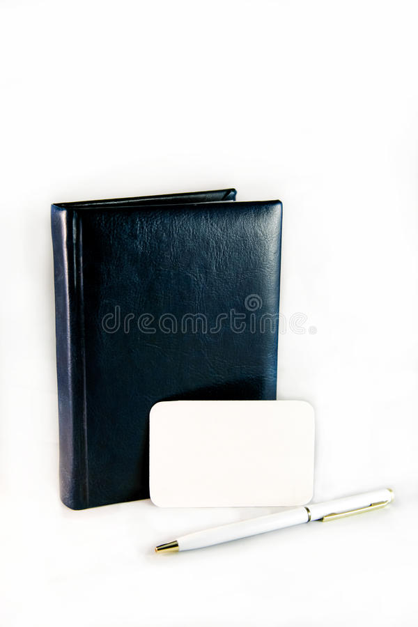 Leather dark diary and white pen near a blank card for writing. Leather blue dark diary and white pen near a blank card for writing royalty free stock photography