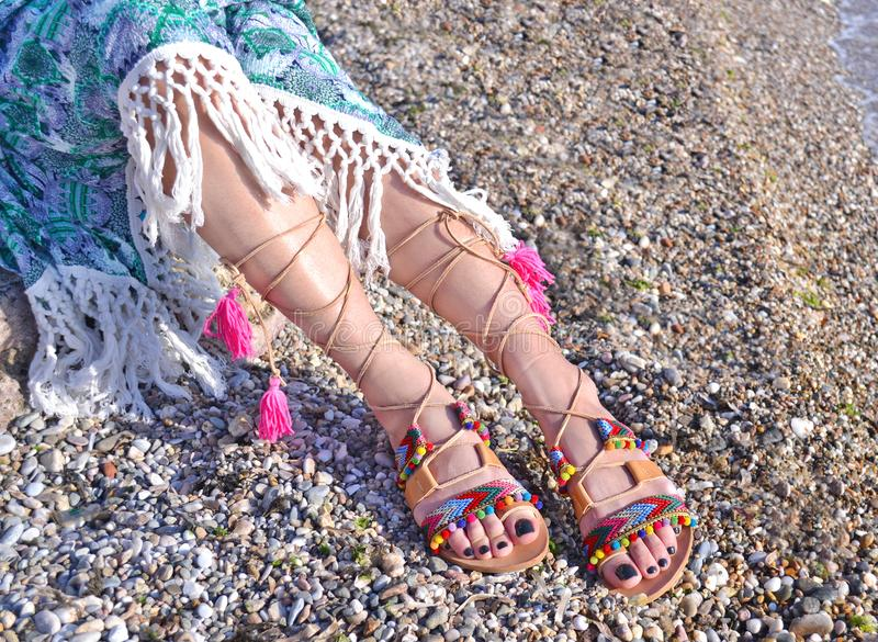 Leather greek sandals advertisement on the beach. Bohemian style clothing stock image