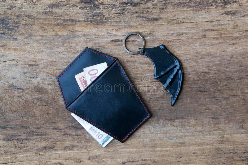 Leather holderand key ring. Leather holder for money and card in the shape of a coffin and key ring in bat wing shape royalty free stock photos