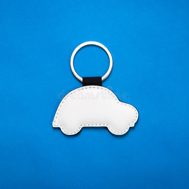 Leather key ring in car shape on blue paper background. Blank key chain for your design. Leather key ring in car shape on blue paper background. Blank key chain stock images