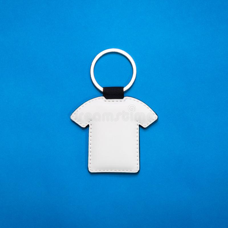 Leather key ring in shirt shape on blue paper background. Blank key chain for your design. Leather key ring in shirt shape on blue paper background. Blank key royalty free stock image