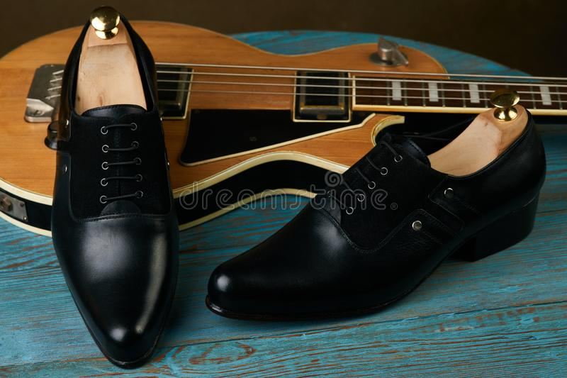 Leather mens shoes and bass guitar over brown background with copy space royalty free stock photography