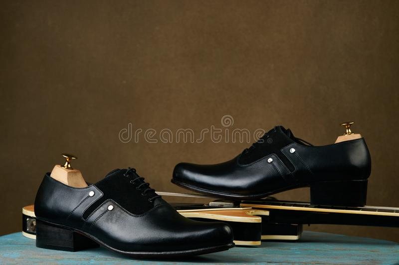 Leather mens shoes and bass guitar over brown background with copy space stock photography