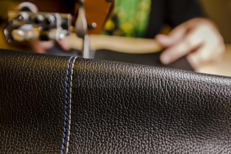 Leather Piece in Foreground with Blue and White Stitching on a Commercial Sewing Machine royalty free stock photo