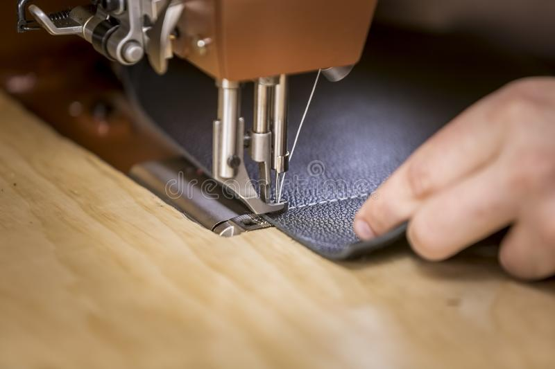Leather Piece Stitched on a Commercial Sewing Machine. Black leather piece on industrial sewing machine showing even white stitches royalty free stock photo