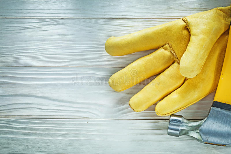 Leather protective glove claw hammer on wooden board stock image