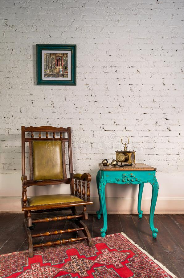 Leather rocking chair, wooden green vintage table and antique golden telephone set over bricks wall stock photo
