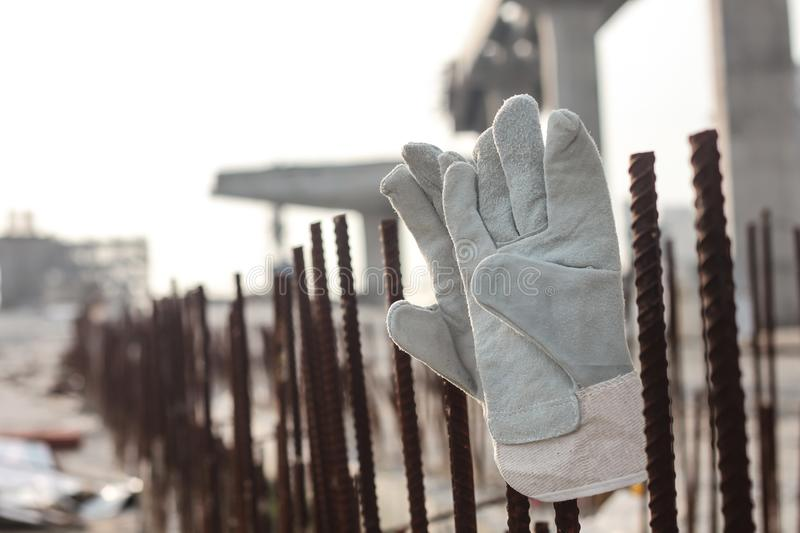 Leather safety gloves on construction working site background. Business construction concept royalty free stock image