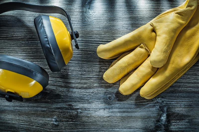 Leather safety gloves noise reduction earmuffs on wooden board.  stock image