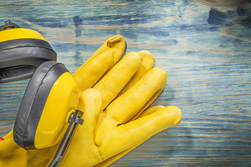 Leather safety gloves noise reduction earmuffs on wooden board c. Onstruction concept stock photos