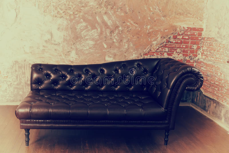 Leather sofa in the English style in the room with old vintage b. Leather sofa in the English style in the room with old vintage red brick walls stock photography